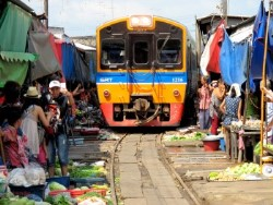 Train passing through Maeklong Railway Market