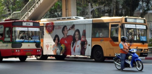 A red / cream regular bus and an orange air-conditioned bus on the streets of Bangkok