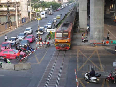 An ordinary train passing the Asok Din Daeng level crossing in Bangkok