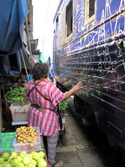 Vendors standing in between the train and the market-stalls